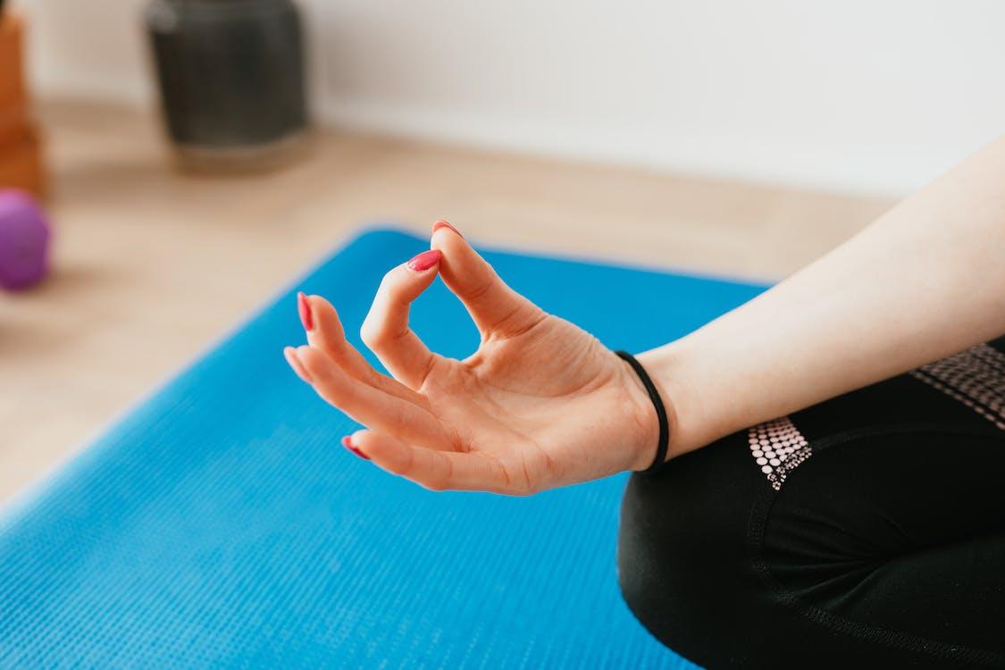 Crop faceless lady sitting in Zen pose on yoga mat