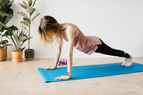 Unrecognizable woman in tracker standing in Phalakasana pose in flat