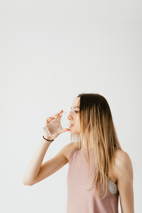 Concentrated young fit female in sport top drinking water from glass while standing against white background