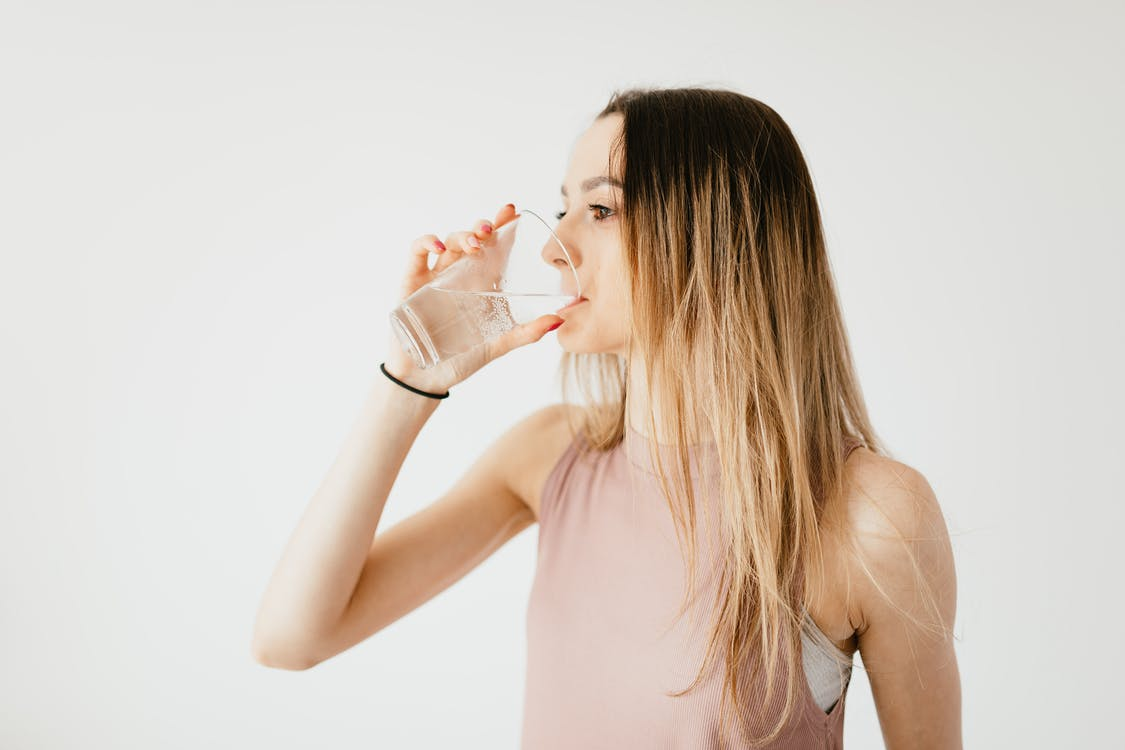 Young thirsty fit female with long hair in sportswear drinking water while recreating after workout