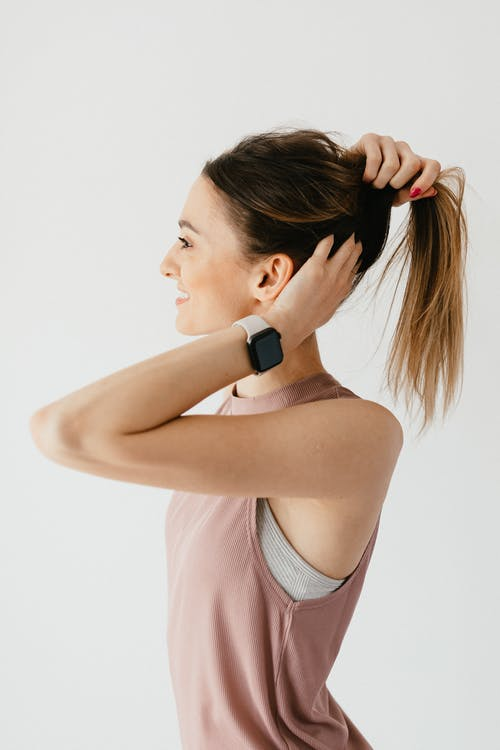 Positive young woman collecting hair in tail