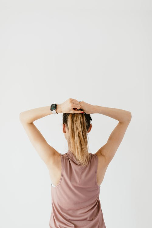 Unrecognizable woman making ponytail against white background