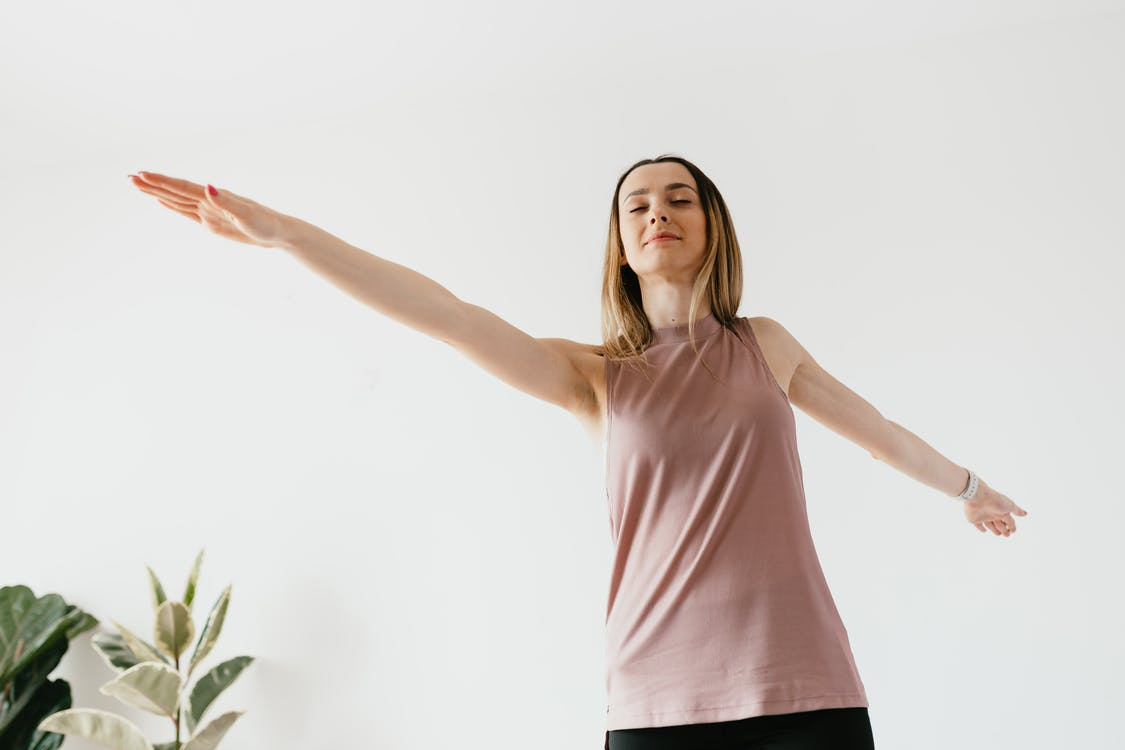 Positive young woman doing balancing exercise during training at home