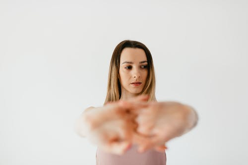 Concentrated woman stretching clasped hands
