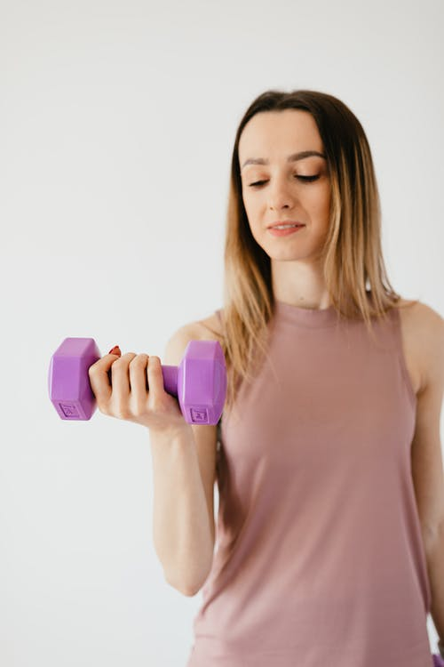 Strong young female athlete exercising with dumbbell