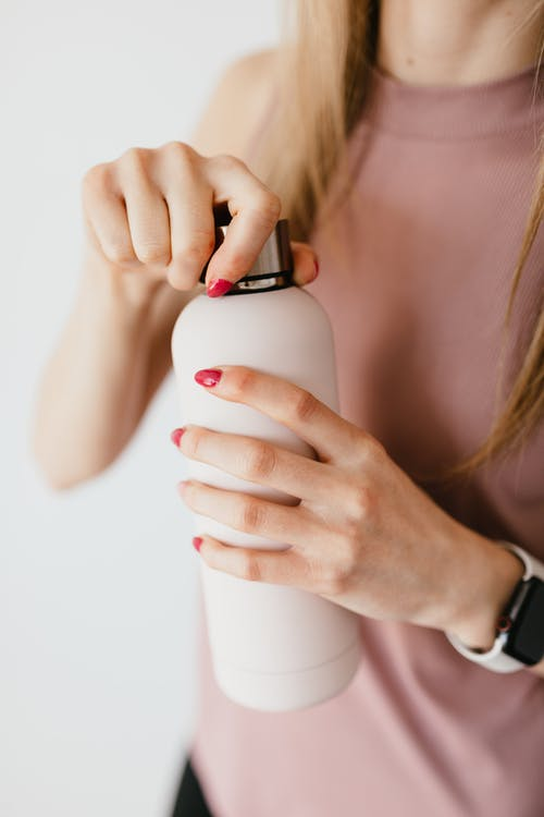 Unrecognizable woman with red nails opening cosmetic bottle against white background