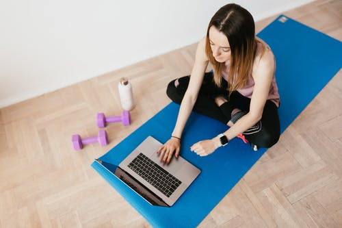 Young woman with laptop sitting on yoga mat