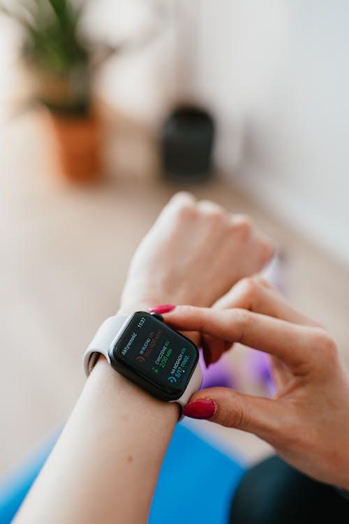 Crop woman using smart watch on yoga mat