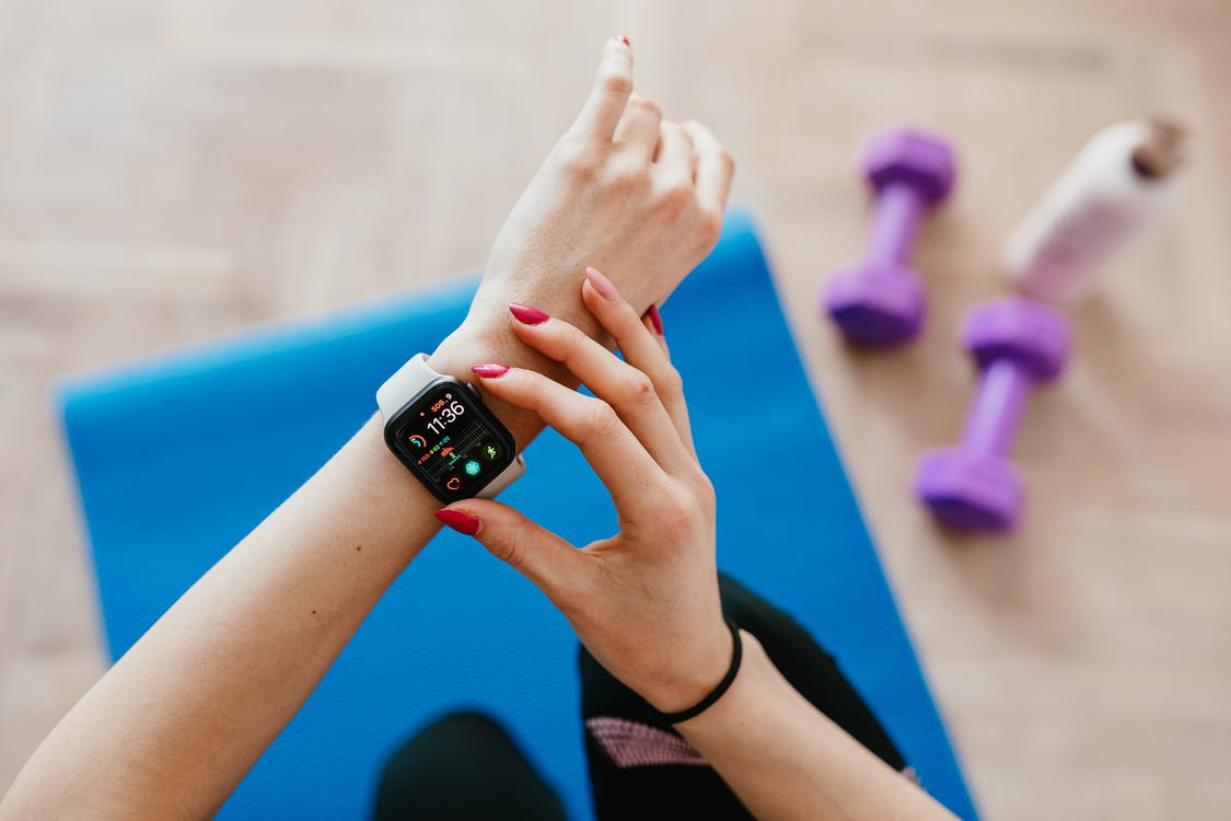 Anonymous sportswoman checking smart watch and sitting on mat