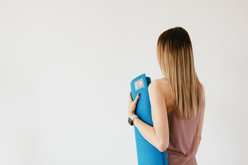 Young woman with yoga mat in hand