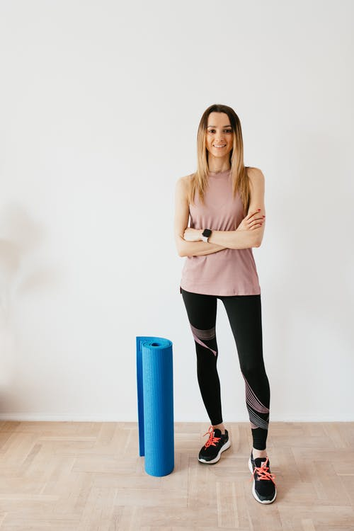 Slim sportswoman with folded yoga mat at home
