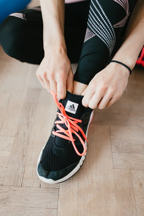 From above young anonymous female athlete in leggings adjusting sneakers while sitting on wooden floor in modern fitness studio and preparing for training