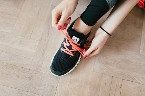 Crop sportswoman tying shoelaces on floor