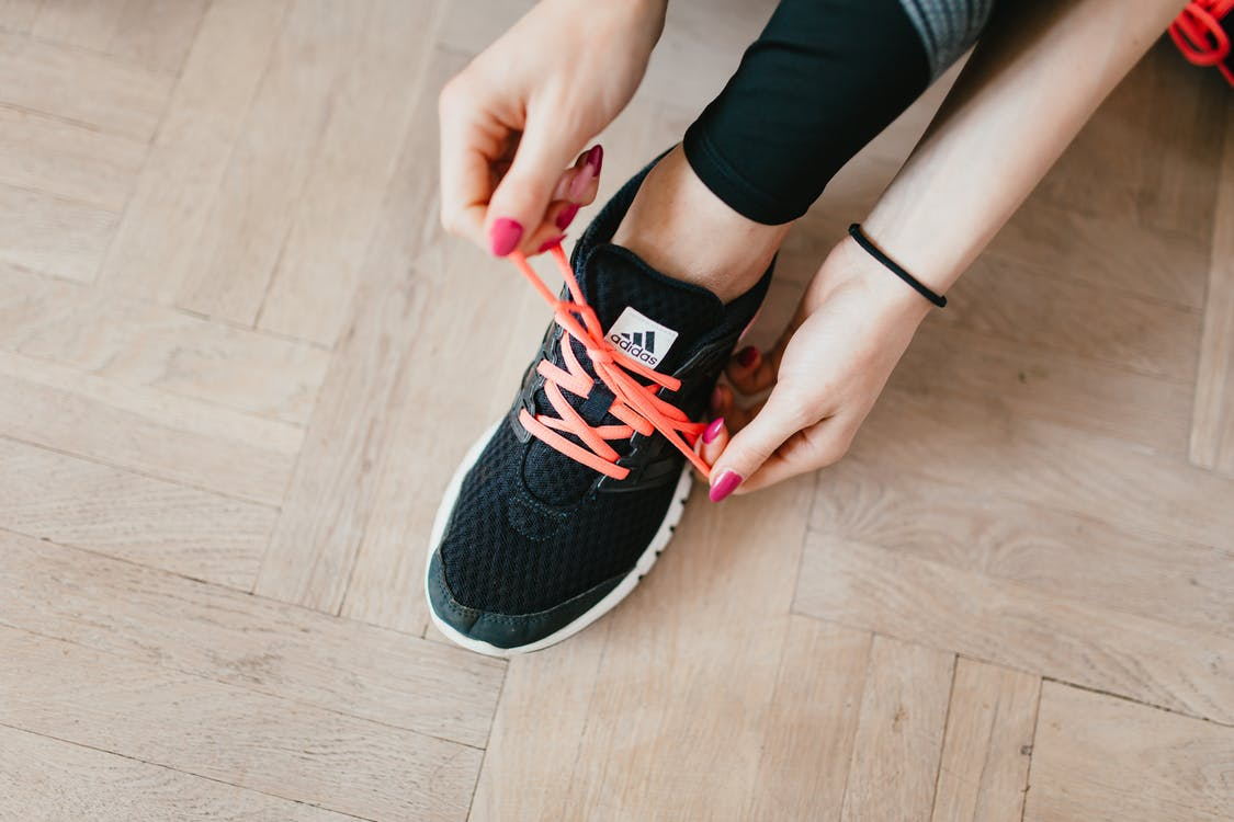 Top view of young anonymous female athlete in leggings tying shoelaces on sneakers while sitting on wooden floor in modern fitness studio and preparing for training