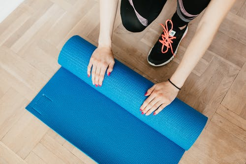 Crop young sportswoman unfolding blue yoga mat