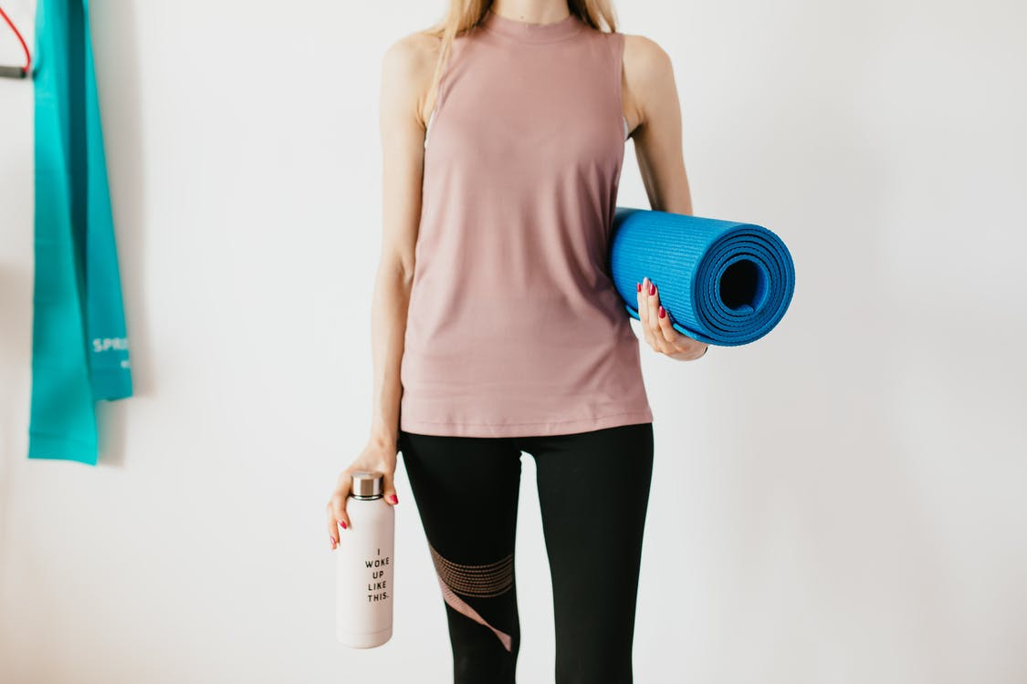 Faceless slim female athlete in sportswear standing with blue fitness mat and water bottle while preparing for indoors workout