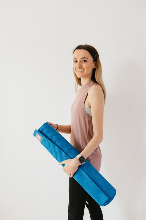 Side view of female athlete in sportswear carrying blue sport mat against white wall and looking at camera over shoulder while preparing for fitness training indoors