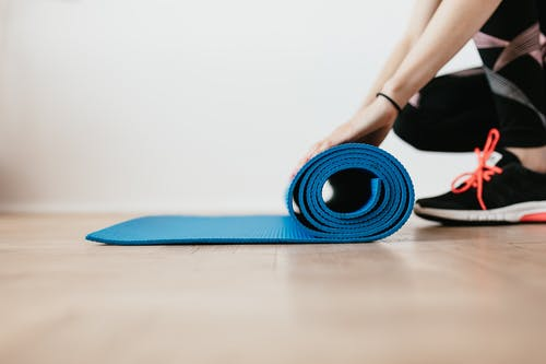 Crop young sportswoman unfolding blue fitness mat