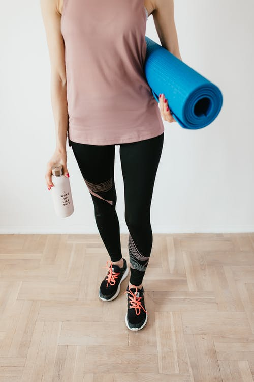 Crop fit female athlete in sportswear standing with blue fitness mat and water bottle while preparing for home exercising in morning