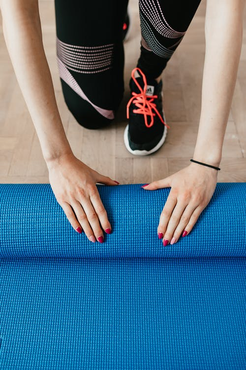 From above of anonymous female athlete in black leggings and sneakers unfolding blue mat for exercising on wooden floor in modern fitness studio