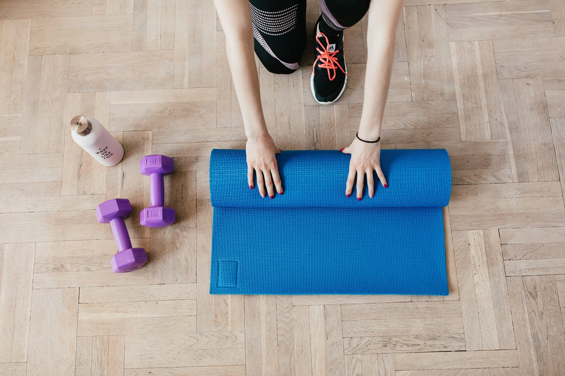 Top view of anonymous female athlete in black leggings and sneakers unfolding blue mat for exercising on floor near dumbbells and water bottle in modern fitness center