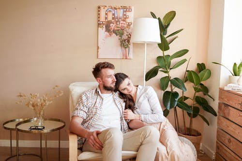 Bearded man sitting with young girlfriend in casual wear in comfortable chair near potted plant at home and looking away