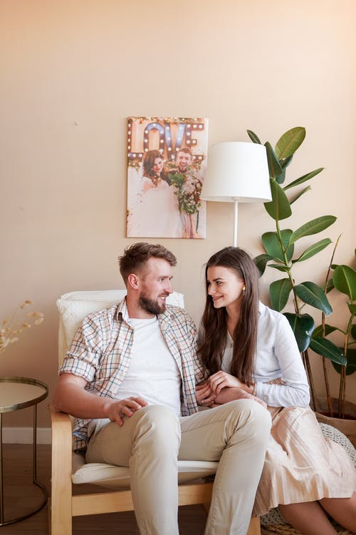 Happy couple having conversation while sitting in chair at home