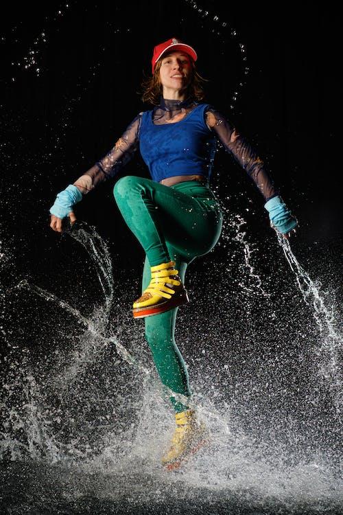 Energetic young woman dancing in water