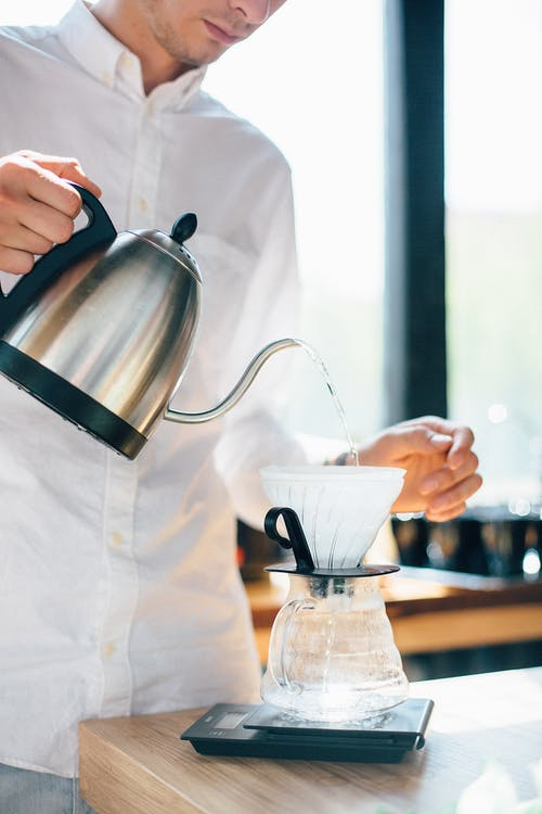 Person Pouring Milk on White Ceramic Cup