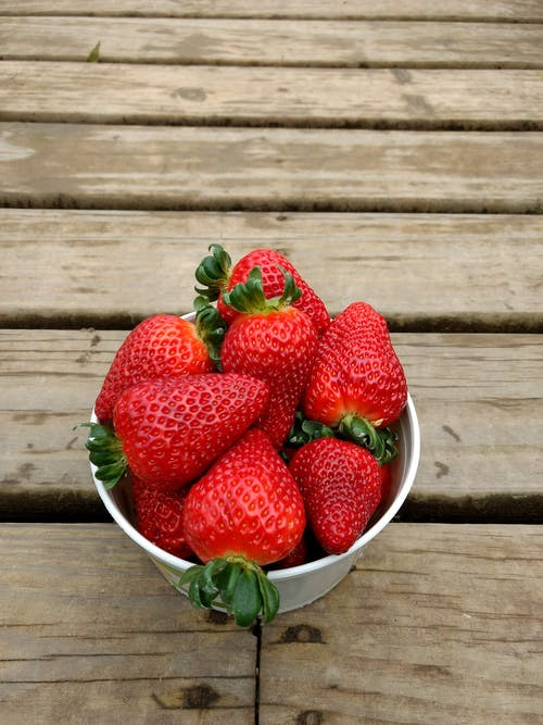 From above of big ripe strawberries with green tails placed in white bowl on lumber board  during seasonal harvest