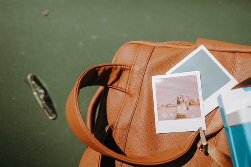 緑の床に茶色の革のハンドバッグ
