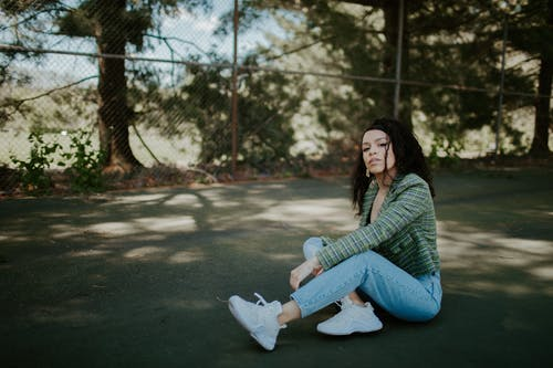 Woman in Green Sweater and Blue Denim Jeans Sitting on Ground
