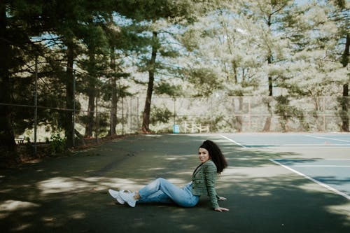 Woman in Gray Long Sleeve Shirt and Blue Denim Jeans Sitting on Gray Concrete Road during