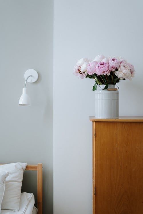 Pink and White Flowers in White Ceramic Vase on Brown Wooden Table