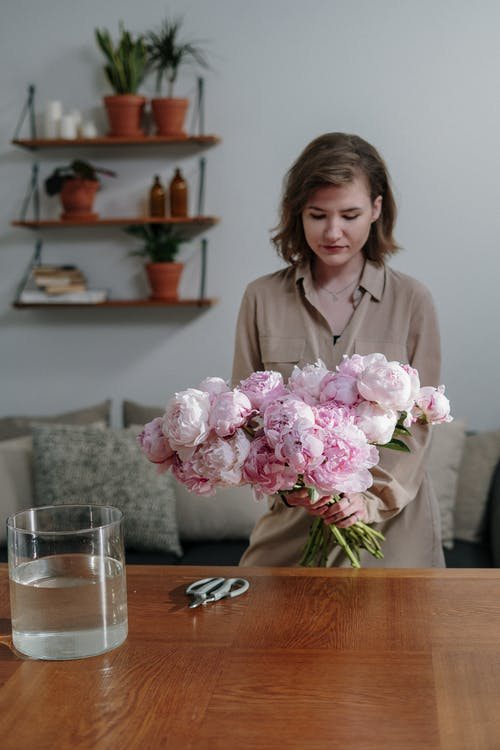 Woman in Pink Dress Shirt Sitting Beside Brown Wooden Table With Pink Flowers