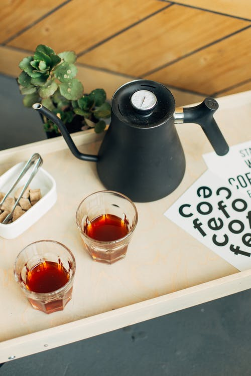 Tray with glasses of hot black tea and teapot