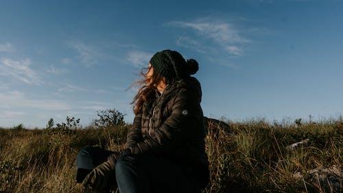 Woman in Black Jacket Sitting on Grass Field