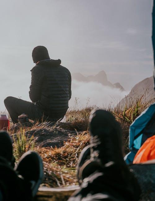 Man in Black Jacket Sitting on Brown Grass