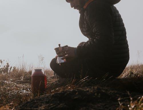 Man in Black Jacket Holding Smartphone Sitting on Ground