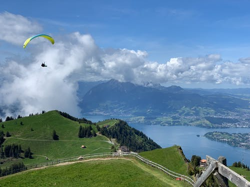 Person Paragliding Over Mountain
