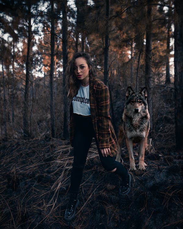 Woman in Black Jacket Standing Beside Brown and Black Dog Surrounded by Trees