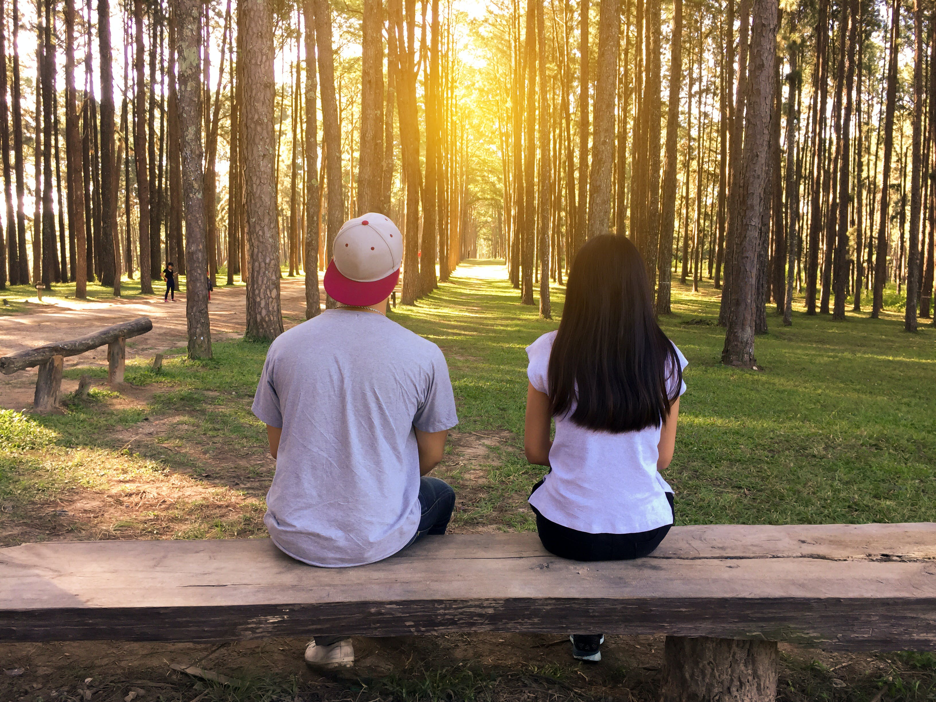 Man and Woman Sitting on Bench in Woods