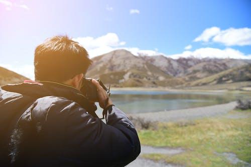 Man Taking Photo of Mountain