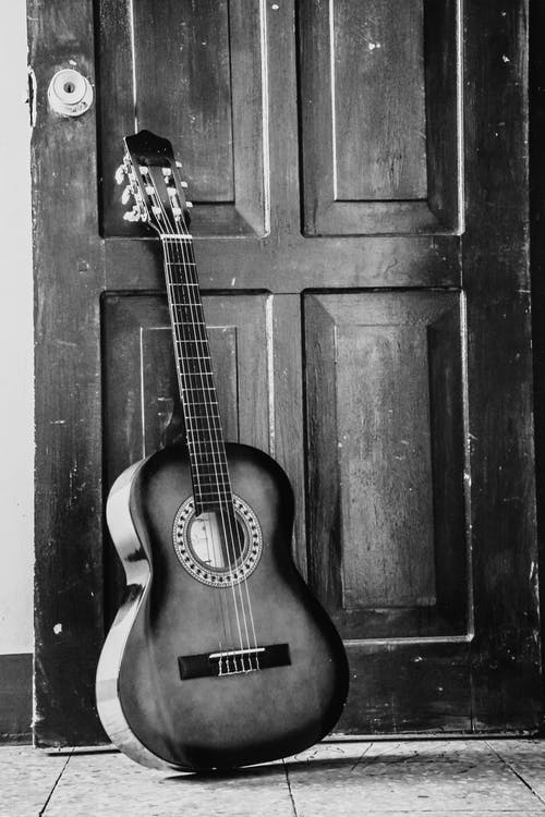 Black and white acoustical guitar with dark sides placed on concrete floor near shabby door of old building