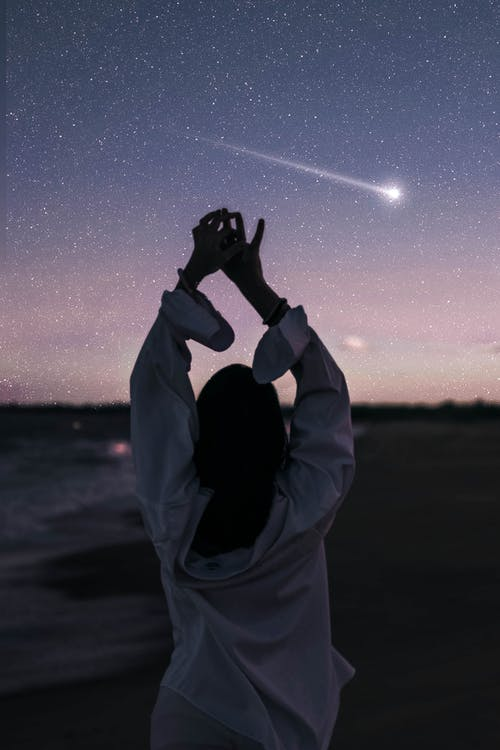 Unrecognizable woman with raised hands at dusk