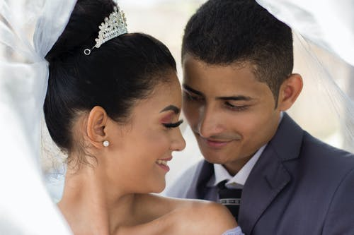 Happy newlywed ethnic couple in wedding suits