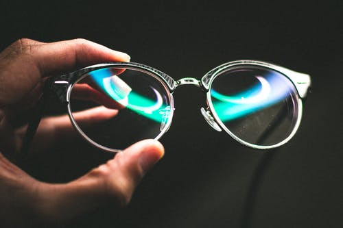 Faceless person holding trendy glasses against black background