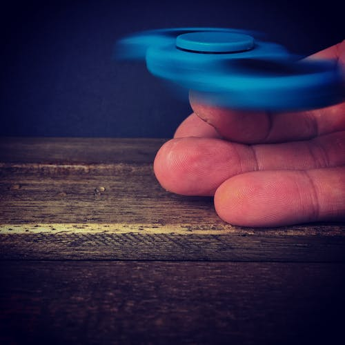 Person Playing Blue Hand Spinner