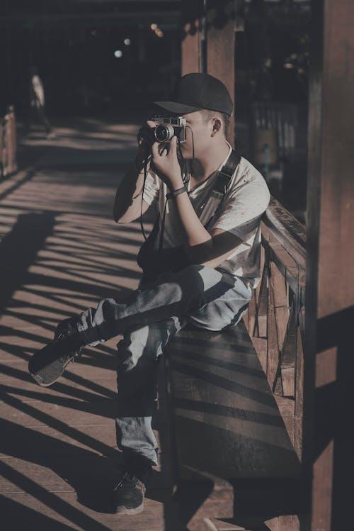 Photo of Man Sitting on Bench While Taking Photo Using Camera