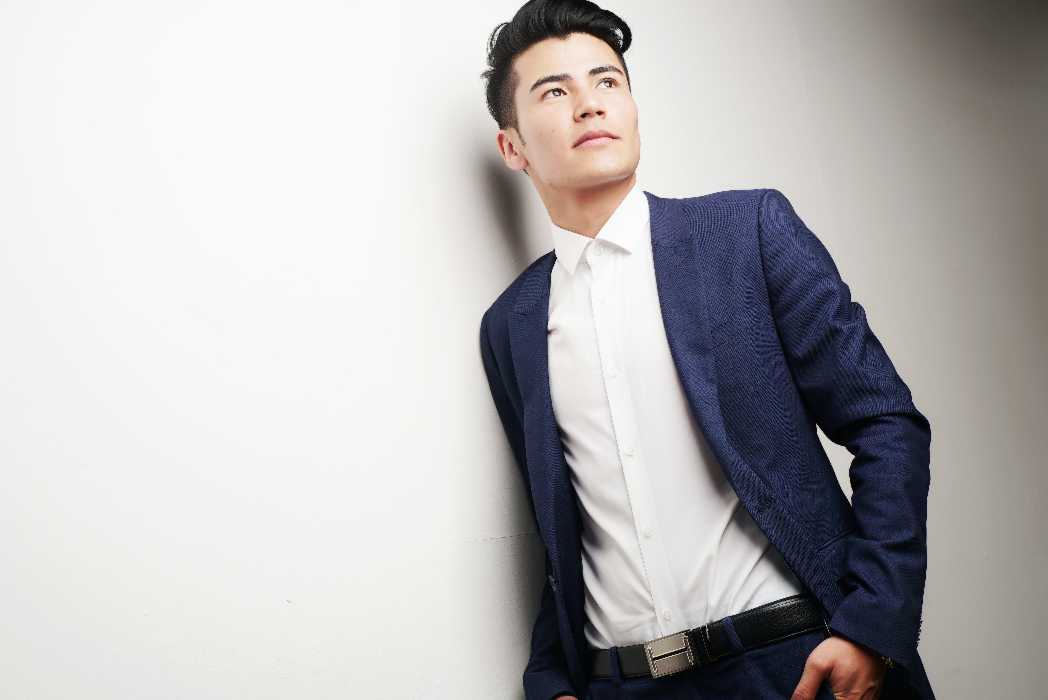 Man Wearing Blue Blazer and White Dress Shirt Leaning on White Wall